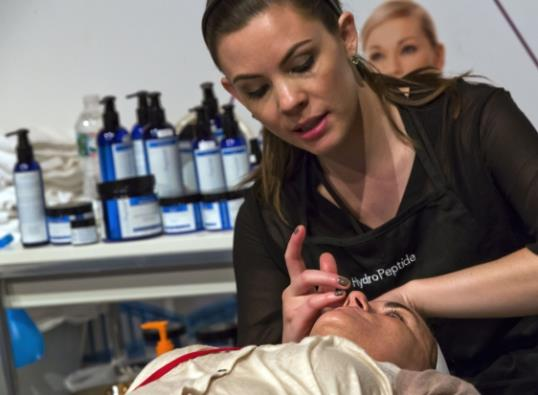 Erin Ferrill, with HydroPeptide, giving a treatment with their anti-aging skin care products, at the International Spa Association event, in New York. (AP Photo/Richard Drew)