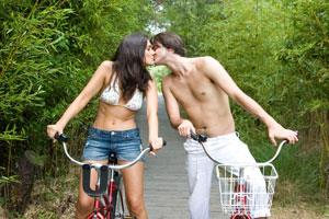 Photo: Couple kissing on bikes // Getty