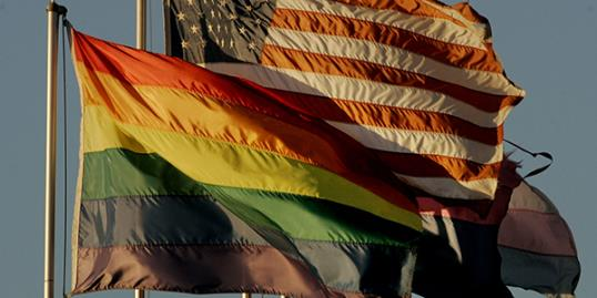 New California law allows transgender students to choose bathrooms. An American flag flies next to a Rainbow flag at the San Diego Lesbian Gay Bisexual Transgender Community Center. (© Sandy Huffaker/Getty Images)