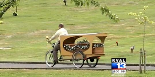 Photo: Still of Wade Lind riding his bicycle hearse (KVAL, http://aka.ms/bicyclehearse)
