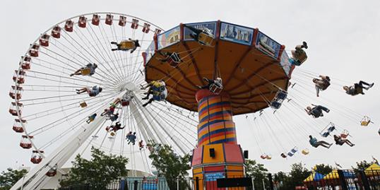 Photo: In this file photo photo, visitors ride on the Ferris Wheel and Wave Swinger at Chicago's nearly century-old Navy Pier. (AP Photo/Charles Rex Arbogast, File)