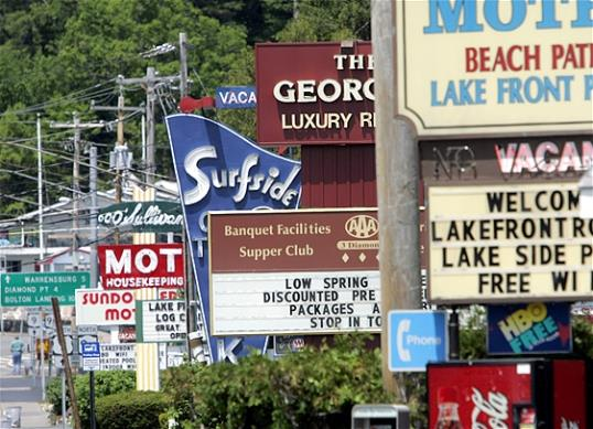 Photo: In this May 2009 file photo, motel signs are seen in Lake George, N.Y. Airlines, hotels and campgrounds are expecting to see more customers in 2013 than in the previous few summers. (AP Photo/Mike Groll, File)