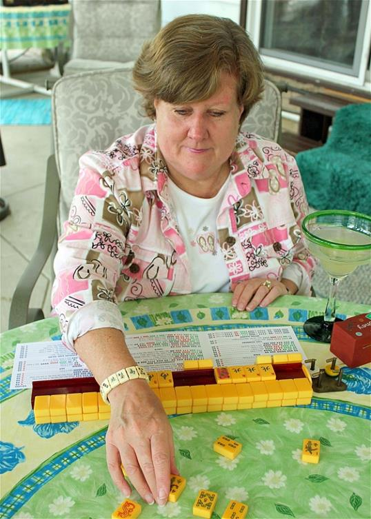 Photo: Judy Palladino handles mahjong pieces during a game night gathering in Mayfield Village, Ohio last month. For the baby boomer generation, getting together to play games is a way to stay active and social. It also can help people stay mentally sharp. (AP Photo/Bonnie Gruttadauria)