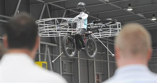 Photo: Two men watch the remote-controlled Flying Bike with a test dummy during its presentation in Prague on Wednesday, June 12, 2013. Three Czech companies have teamed up to make a prototype of an electric bicycle that can fly. (AP Photo/CTK, Stanislav Zbynek)