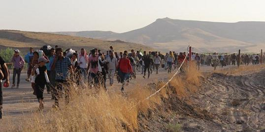 Syrian refugees walk from Syria into the border town of Peshkhabour, Iraq. (© REX/Xinhua/UNHCR/Galiya Gubaeva)