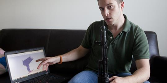 Cody Wilson points to his laptop screen displaying an image of a prototype plastic gun on the screen, while holding in his other a weapon he calls