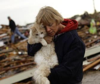 Photo: June Simson holds her cat, Sammi, who she found standing on the rubble of her home. / Getty Images