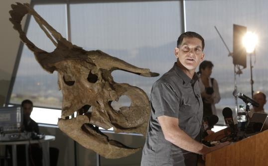 Dinosaur paleontologist Scott Sampson, is shown making remarks as he stands next to a reconstruction of a