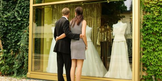 Photo: Younger couple looking at wedding dresses / Manchan/Getty Images