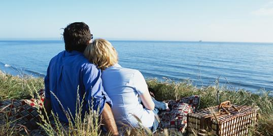 Couple sitting on a bluff above the ocean - Santa Barbara, California (Macduff Everton/Getty Images)