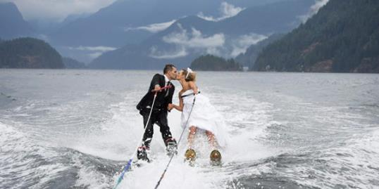 Newlyweds Cam Auge and Caylee Wasilenko share a kiss as they water ski in Bedwell Bay in North Vancouver, British Columbia (Jonathan Hayward/The Canadian Press/AP)