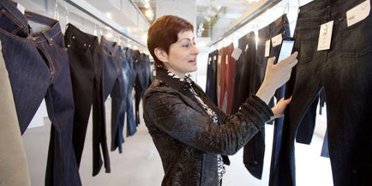 Photo: Nadia Shouraboura uses her smartphone to select a style of jeans. Robotics are used to deliver a customer's choices to a dressing room//Steve Ringman/The Seattle Times