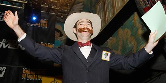 Devon Holcombe of Jacksonville, Fla., greets the crowd before continuing on to win the gold medal in the Natural Moustache division during the fourth annual Just For Men National Beard and Moustache Championships on Saturday in New Orleans.