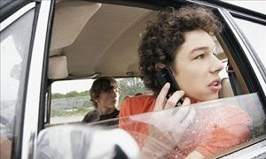 Distracted teen talks on cellphone while driving (© Corbis)