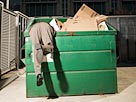 Image: Businessman Searching Through Garbage Container (© Fuse/Getty Images)