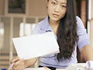Image: Woman with paperwork (© Brand X/SuperStock)