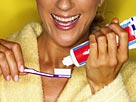 Image: Woman putting toothpaste on toothbrush© Brand X Pictures/Getty Images