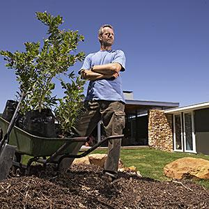 Image: Landscape gardener standing in garden with shrubs and gardening tools. Copyright: Ocean, Corbis, Corbis