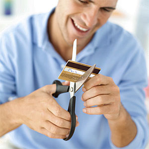 Young man destroying his credit card with a pair of scissors © George Doyle, Stockbyte, Getty Images