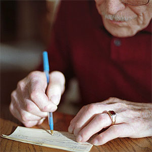 Senior man writing check © Dennis Wise, Photodisc, Getty Images