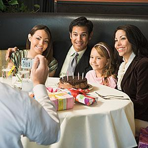 Image: Family sitting at table in restaurant, posing for group photograph © Andersen Ross, Digital Vision, Getty Images