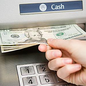 Person withdrawing cash &#169; Image Source/Image Source/Getty Images