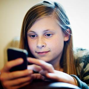 Young girl using smartphone (&#169; Mike Harrington/Lifesize/Getty Images