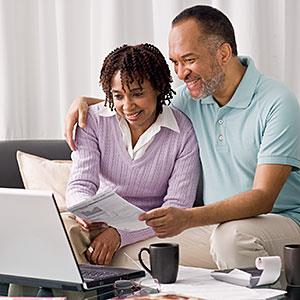 Image: Couple at home paying bills online &#169; DMH Images, Photodisc, Getty Images
