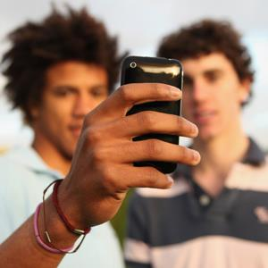 Boys using a smartphone to take a photo (&#169; Juliet White/Digital Vision/Getty Images)