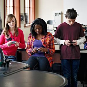 Students using smart phones in classroom (© Thomas Barwick/Iconica/Getty Images)