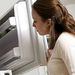 Image: Woman and refrigerator (&#169; Photos.com/Jupiterimages)