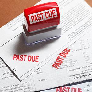Past due stamp sitting on three bills. © Derek E. Rothchild, Stockbyte, Getty Images