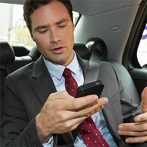 Businessman in car with smartphone (© Image Source, Image Source, Getty Images)