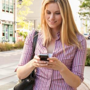 Woman using smart phone in city © ML Harris/Getty Images/Getty Images