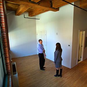 People stand in an empty 374-square-foot apartment in a micro-housing unit in Fort Point, South Boston on Feb. 13, 2013 (© John Tlumacki/The Boston Globe via Getty Images)