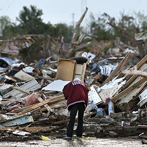 A local resident looks through the rubble of a destroyed home, one day after a tornado moved through Moore, Okla., Tuesday, May 21, 2013 (© Brennan Linsley/AP Photo)