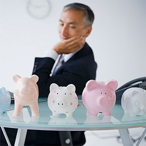 USA, Mid-Atlantic USA, New Jersey, Businessman looking at piggybanks standing on desk © Jamie Grill, Tetra images, Getty Images