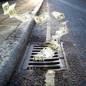 Money falling in a manhole © LdF, Vetta, Getty Images