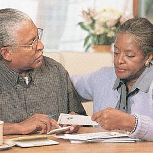Logo: Couple paying bills (Corbis)
