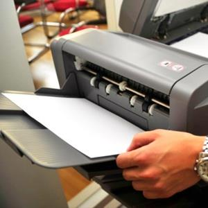 Businessman using printer (© Stephan Zabel/E+/Getty Images)