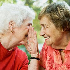 Logo: Two senior women sharing a secret (Image Source, Image Source, Getty Images)