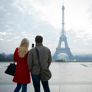 Couple taking photo of Eiffel tower in Paris (© Les and Dave Jacobs/Cultura/Getty Images)