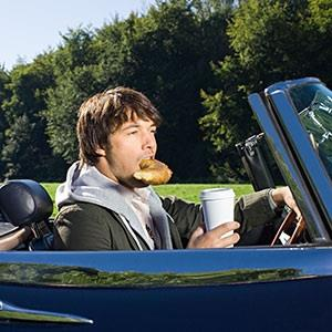 Image: Man eating in car (© Image Source/Corbis/Corbis)
