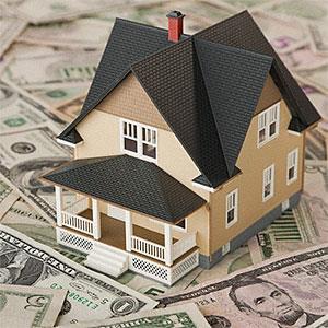 Toy house sitting on money © Vstock, Tetra Images, Corbis