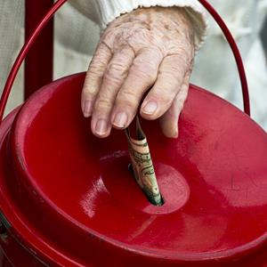 A woman makes a donation into a Salvation Army kettle on November 24, 2012, in Clifton, Va. (© Paul J. Richards/AFP/Getty Images)