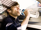 Image: Man drinking bottled water while driving (© PhotoAlto / SuperStock/SuperStock)