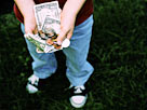 Image: Boy holding allowance money (© Bryan Mullennix/Photodisc/Getty Images)