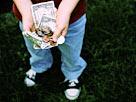 Image: Boy holding allowance money (© Bryan Mullennix/Photodisc/Getty Images)