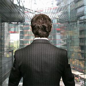 A business man looking out of a glass elevator -- Stella, fStop, Getty Images