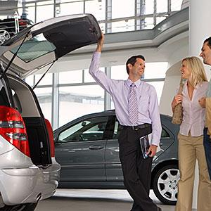Car salesman showing couple new silver hatchback in car showroom, opening boot, smiling, side view copyright Juice Images, Cultura, Getty Images